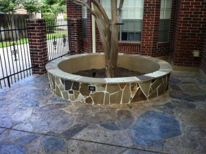 Stamped concrete patio with flagstone around the tree